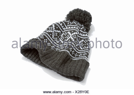 A grey and white woollen bobble hat - Stock Photo