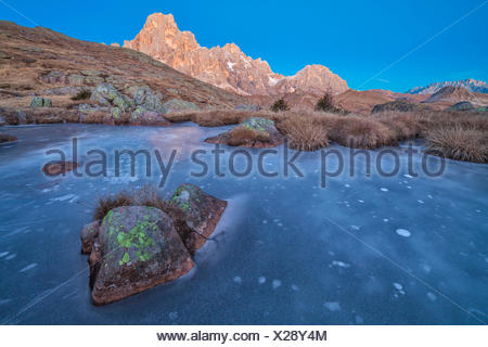 Europe, Italy, Trentino Alto Adige, Icy small pond on Cavallazza Piccola group of Lagorai, In the background the mountain Mulaz and Cimon della Pala, Pale di San Martino, Dolomites - Stock Photo