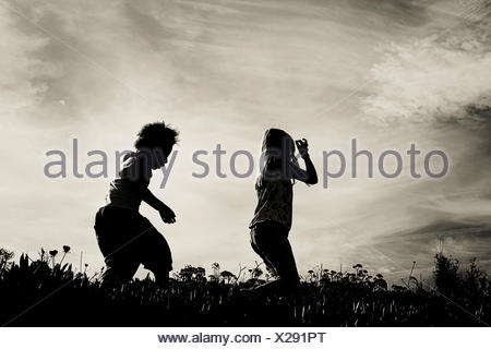 silhouette of two girls running in a field - Stock Photo