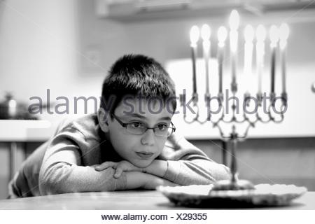 Cute Boy Looking At Lit Candles While Sitting On Table At Home - Stock Photo