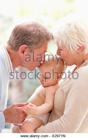 Grandparents holding and kissing baby - Stock Photo