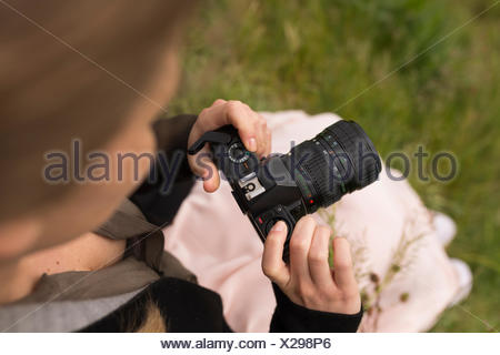 Woman with camera in nature - Stock Photo