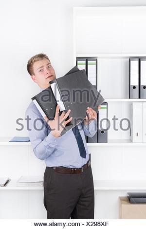 Junger schockierter Geschäftsmann steht vor einem Regal im Büro und hält mehrere Aktenordner in seinen Armen. Der Mann schaut zur Kamera.