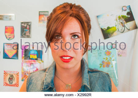 Portrait of young woman gazing upward in kitchen - Stock Photo