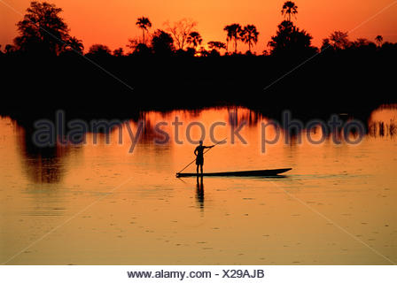 Boatman on the Chobe River at Sunset, Botswana, Africa - Stock Photo