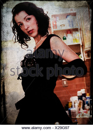 A young woman with dark hair wearing a black dress - Stock Photo