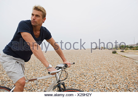 A man riding a bicycle on a shingle beach. - Stock Photo