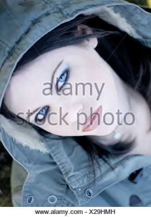 A sinister looking pale-skinned young woman with piercing blue eyes and a hooded coat - Stock Photo