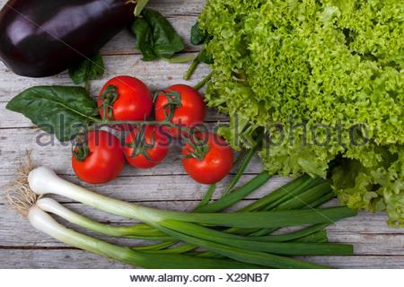 Top view of table with fresh spring vegetables, base ingredients in a diet: lettuce, tomatoes, green onions, spinach and eggplant. - Stock Photo