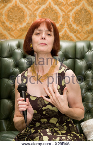 Mature lady singing at home - Stock Photo