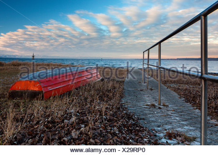 Red lifeboat lying upside down on the shore of Lake Constance near Hoernle mountain, Constance, Konstanz, Baden-Wuerttemberg - Stock Photo