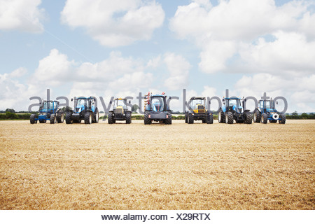 Tractor harvesting grains in crop field - Stock Photo