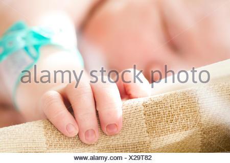 Sleeping baby girl's (0-1 months) hand on cradle - Stock Photo