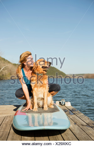 A woman and a retriever dog on a paddleboard on the jetty. - Stock Photo