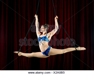 Studio shot of female aerialist performing splits on ropes - Stock Photo
