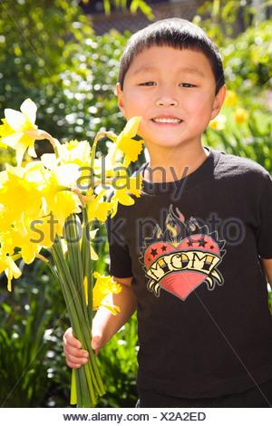 Boy holding daffodils in garden - Stock Photo
