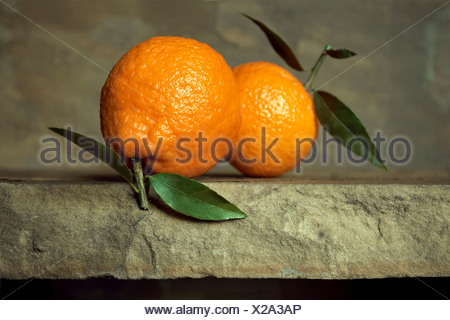 Two oranges with leaves on stone background - Stock Photo