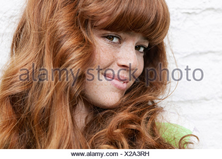 Germany, Berlin, Close up of young woman, smiling, portrait - Stock Photo