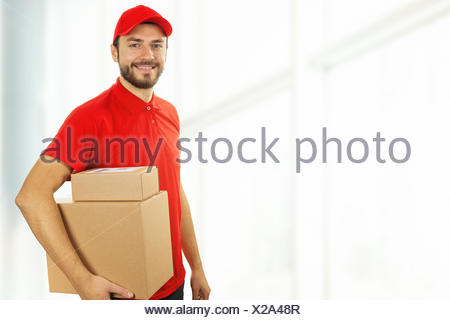 delivery man with cardboard boxes standing in office. copy space - Stock Photo