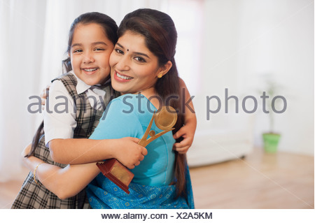 Woman and her daughter hugging each other and smiling - Stock Photo
