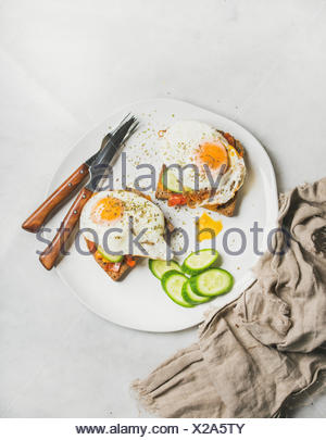 Breakfast toast with fried eggs with vegetables on white plate over grey marble background, top view. Healthy, clean eating, dieting food concept - Stock Photo