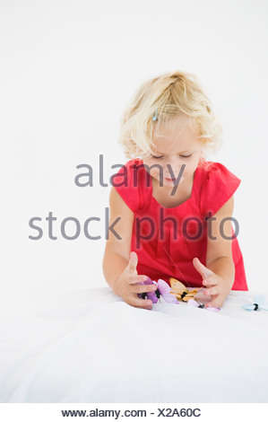 Girl playing with artificial butterflies - Stock Photo
