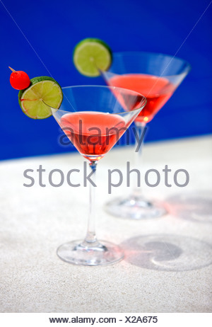 cocktails in martini glasses by a swimming pool - Stock Photo