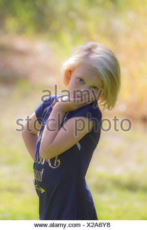 Pretty blonde young girl, posing and looking at camera, in back light sunshine. Cranbrook, BC, Canada - Stock Photo