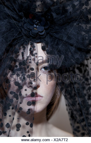 Close-up portrait of a young woman wearing black veil - Stock Photo