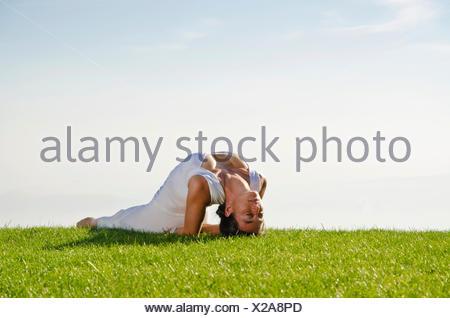 Young woman practising Hatha yoga, here the pose matsyasana, fish - Stock Photo