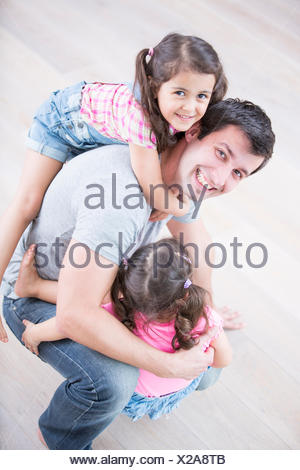 High angle portrait of playful father carrying girls at home - Stock Photo