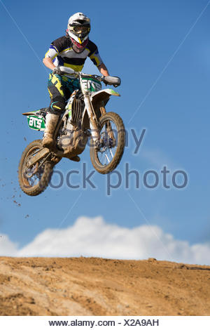 Young male motocross racer jumping muddy hill - Stock Photo