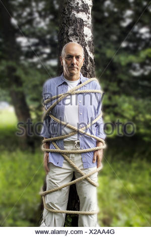 Garden, trunk, senior, tied up man, tree, bound, fastenedly, rope, cable, cord, helplessness, helplessly, defenceless, caught, trapped, hopelessness, hopelessly, maneuver, defenceless, powerless, defencelessness, powerlessness - Stock Photo