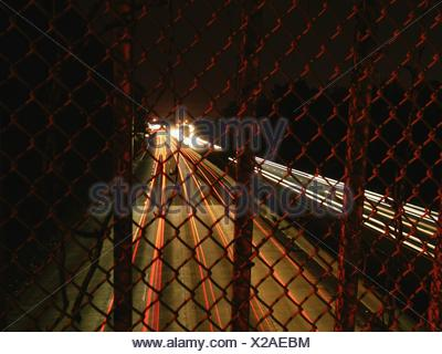 Illuminated Vehicle Light Trails On Highway Seen From Chainlink Fence - Stock Photo