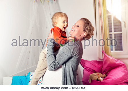 Germany, Bonn, Pregnant mother carrying son, smiling - Stock Photo
