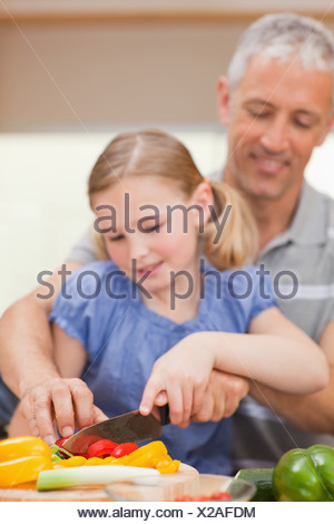 Portrait of a father slicing pepper with his daughter - Stock Photo