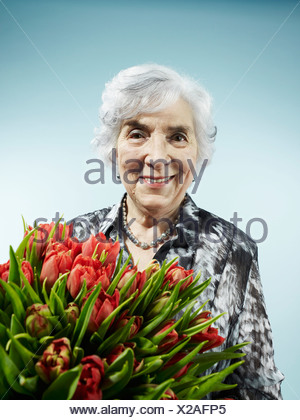 A senior woman receiving a bouquet of tulips - Stock Photo