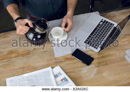 Partial view of man pouring coffee in cup on desk with laptop and newspapers - Stock Photo