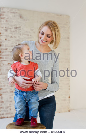 Studio portrait of mother holding baby daughter on stool - Stock Photo