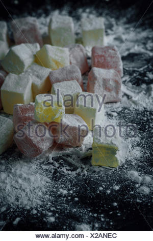 Classic Turkish delights in two colors dusted with starch, one of which is bitten. - Stock Photo