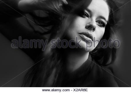Close-Up Of Beautiful Young Woman With Hand In Hair Against Gray Background - Stock Photo