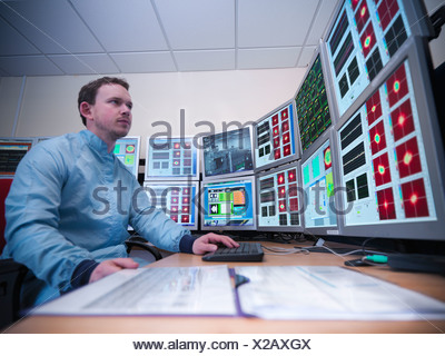 Scientist working on computers in lab - Stock Photo