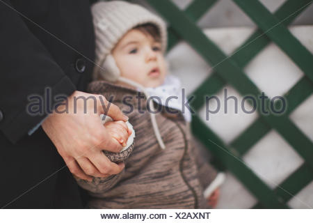 Father holding baby son's hand - Stock Photo