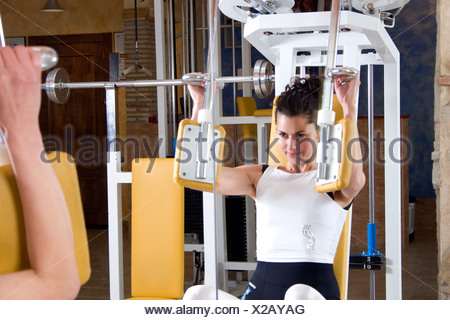 dark haired young woman working out in gym - Stock Photo