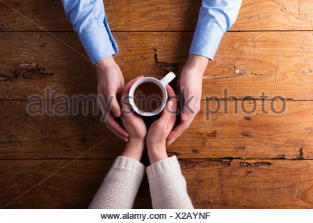 Hands of a young couple holding mug of tea - Stock Photo