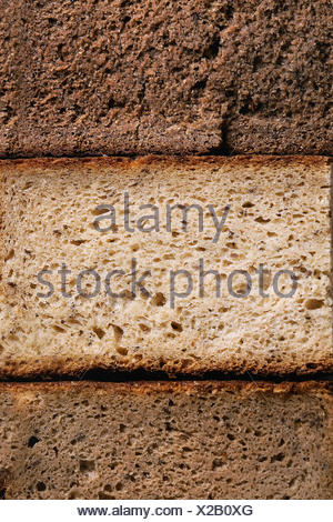 Variety loaves of sliced homemade rye bread whole grain. Top view, close up. Healthy eating food background - Stock Photo