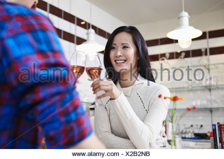 Germany, Cologne, Young couple drinking wine, smiling - Stock Photo