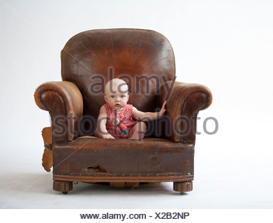 ... Baby Sitting In Old Leather Chair   Stock Photo
