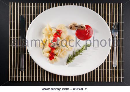 Rosemary garnish on conchiglie pasta with mushrooms - Stock Photo