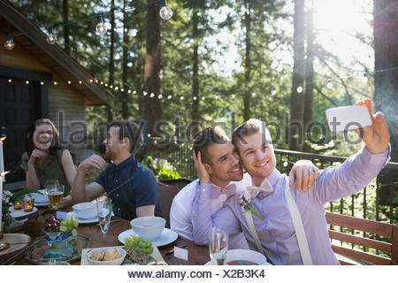 Homosexual couple taking selfie at wedding reception - Stock Photo